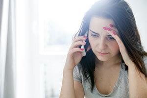 Frau am Handy mit Kopfschmerzen