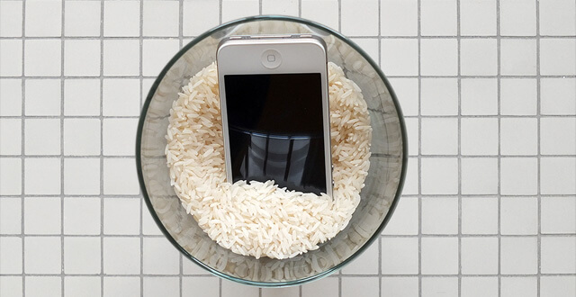 Handy in einer mit Reis befüllten Schale