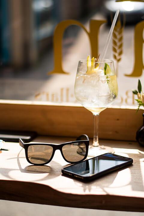 Handy mit Getränk und Sonnenbrille