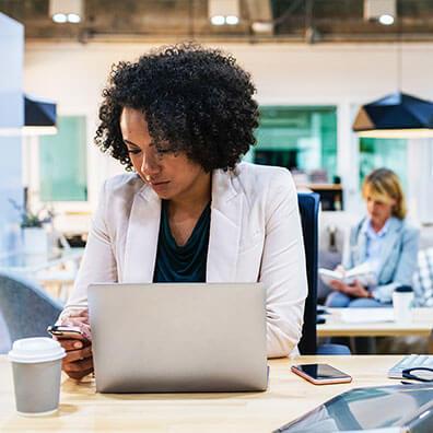 Frau am Handy am Arbeitsplatz